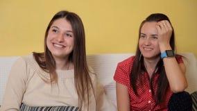 Duas moças sentam-se em casa no sofá, em um dia chuvoso olhando uma comédia, a fala e o riso Noite, casa, conforto video estoque