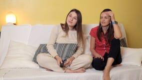 Duas moças sentam-se em casa no sofá, em um dia chuvoso olhando uma comédia, a fala e o riso Noite, casa, conforto vídeos de arquivo