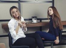 Duas moças têm uma estadia do café no contador em um café Fotografia de Stock Royalty Free
