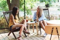 Duas mo?as alegres que sentam-se no caf? fora fotos de stock royalty free