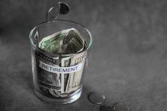 Duas moedas que caem em um vidro encheram-se do dinheiro Imagem de Stock