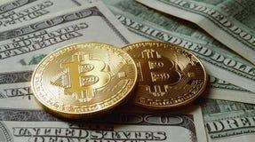 Duas moedas simbólicas do bitcoin em cédulas de cem dólares Foto de Stock Royalty Free