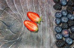 Duas morangos cortadas na madeira Fotografia de Stock