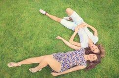 Duas morenas bonitas que encontram-se na grama Imagem de Stock
