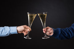 Duas mãos masculinas que guardam vidros do champanhe Foto de Stock Royalty Free