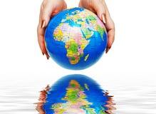 Duas mãos que prendem um globo Fotos de Stock Royalty Free