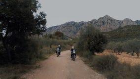 Duas motocicletas offroad conduzem na estrada do cascalho filme