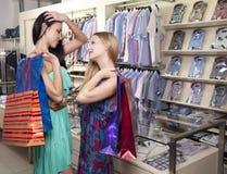 Duas mulheres à moda com reunião dos paperbags na alameda Fotografia de Stock Royalty Free
