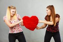 Duas mulheres agressivas que têm discutem a luta que guarda o coração fotografia de stock