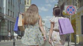Duas mulheres alegres com sacos de compras que andam através da rua da cidade Moças que vestem os vestidos à moda do verão que ap video estoque