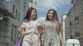 Duas mulheres alegres com sacos de compras que andam através da rua da cidade Moças que vestem os vestidos à moda do verão que ap filme