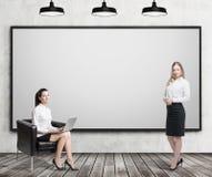 Duas mulheres aproximam o whiteboard Fotografia de Stock Royalty Free