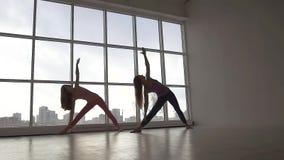 Duas mulheres aptas dos jovens que praticam a ioga levantam synchronously estar contra o fundo da janela vídeos de arquivo