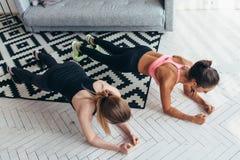 Duas mulheres aptas que estão na posição da prancha sobre o assoalho que reforça o núcleo muscles em casa a vista superior imagem de stock royalty free