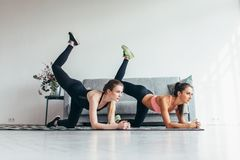 Duas mulheres aptas que fazem o asno dobrado do joelho retrocedem o exercício em toda a posição dos fours que dá certo suas nádeg fotografia de stock