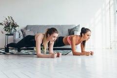 Duas mulheres aptas que fazem a prancha exercitam no assoalho em casa que treina para trás e pressionam os músculos, esporte, exe foto de stock