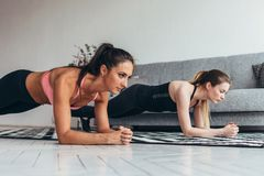 Duas mulheres aptas que fazem a prancha exercitam no assoalho em casa que treina para trás e pressionam os músculos, esporte, exe imagem de stock