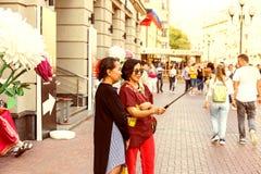 Duas mulheres asiáticas adultas que tomam um selfie usando o smartphone imagem de stock royalty free