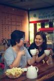 Duas mulheres asiáticas dos amigos que bebem na cafetaria imagens de stock