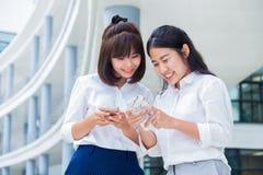 Duas mulheres asiáticas novas apreciam meios sociais em seus telefones espertos d foto de stock