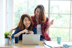 Duas mulheres asiáticas novas que guardam o cartão de crédito e que usam os comp(s) do portátil foto de stock