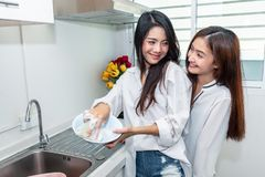 Duas mulheres asi?ticas que lavam pratos junto na cozinha Povos e conceito dos estilos de vida Orgulho de LGBT e tema das l?sbica imagem de stock