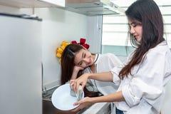 Duas mulheres asi?ticas que lavam pratos junto na cozinha Povos e conceito dos estilos de vida Orgulho de LGBT e tema das l?sbica fotos de stock royalty free