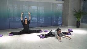 Duas mulheres atléticas que esticam os pés, inclinam-se para a frente sentando no separações na esteira no gym perto da parede me video estoque