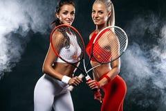 Duas mulheres atleta e jogadores de tênis no fundo preto Conceito do esporte e do tênis foto de stock royalty free