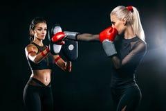 Duas mulheres atleta e pugilista que trainging antes da luta no fundo preto Esporte e conceito de encaixotamento imagem de stock
