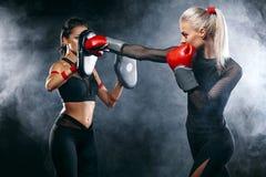 Duas mulheres atleta e pugilista que trainging antes da luta no fundo preto Esporte e conceito de encaixotamento imagens de stock royalty free