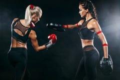 Duas mulheres atleta e pugilista que trainging antes da luta no fundo preto Esporte e conceito de encaixotamento fotos de stock royalty free