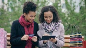 Duas mulheres atrativas da raça misturada com os sacos de papel que sentam-se no banco e que usam o tablet pc e cartão de crédito vídeos de arquivo