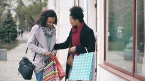 Duas mulheres atrativas da raça misturada com sacos de compras encontram-se surpisely na rua perto da loja da alameda video estoque