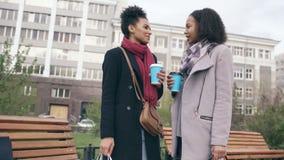 Duas mulheres atrativas da raça misturada com sacos de compras que bebem o coffe e que falam na rua Moças que sorriem e vídeos de arquivo
