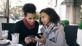 Duas mulheres atrativas da raça misturada que têm a compra em linha com cartão de crédito e smartphone ao falar e ao beber o café fotografia de stock royalty free