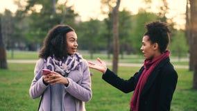 Duas mulheres atrativas da raça misturada têm surpisely a reunião no parque perto da loja da alameda imagens de stock