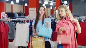 Duas mulheres atrativas que tentam em vestidos e em bolsas na frente de um espelho em uma grande loja de roupa video estoque