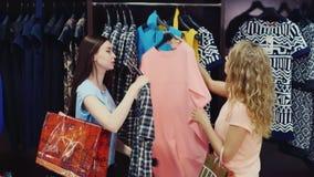 Duas mulheres atrativas vão junto com a roupa estão, olhando vestidos vídeos de arquivo