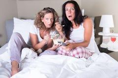 Duas mulheres attratcive que sentam-se na cama e na tevê de vista Foto de Stock Royalty Free