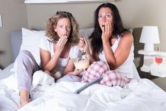 Duas mulheres attratcive que sentam-se na cama e que veem um filme assustador Imagem de Stock