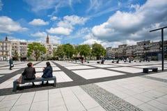Duas mulheres bebem o café no banco moderno sob nuvens Fotos de Stock