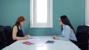Duas mulheres bonitas assinam o contrato no escritório vídeos de arquivo