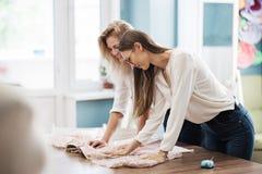 Duas mulheres bonitas devista que vestem as camisas brancas estão inclinando-se sobre a tabela costurando Forma, a oficina do alf imagem de stock