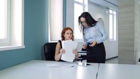 Duas mulheres bonitas discutem a conclusão dos detalhes do tratado no escritório vídeos de arquivo