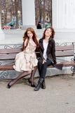 Duas mulheres bonitas em um parque sentam-se em um banco Foto de Stock