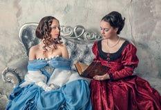 Duas mulheres bonitas em vestidos medievais no livro de leitura do sofá Fotografia de Stock