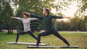Duas mulheres bonitas estão fazendo a ioga fora no parque nas esteiras que praticam asanas e que respiram o ar fresco Prática ind video estoque