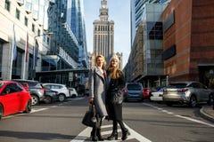 Duas mulheres bonitas estão no centro da cidade e do sorriso dentro imagem de stock royalty free