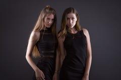 Duas mulheres bonitas na forma preta da noite vestem o levantamento em um fundo cinzento fotos de stock royalty free